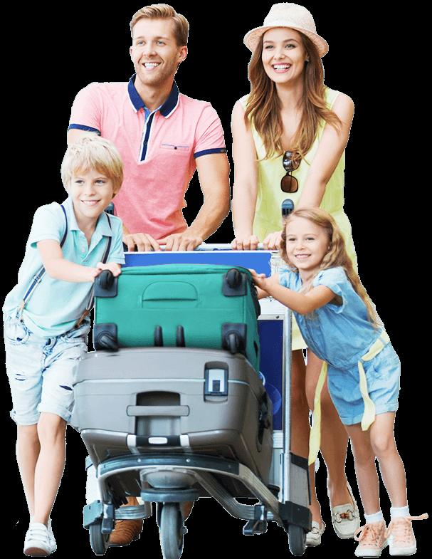 Eine Familie schiebt lachend zusammen einen Kofferwagen mit zwei großen Reisekoffern darauf. Der Vater, die Mutter, ein Junge und ein Mädchen sind alle in Sommersachen gekleidet.